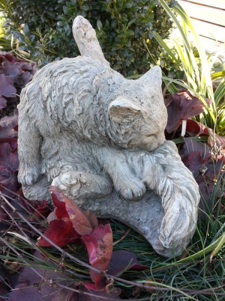 Katze putzt sich aus Steinguss